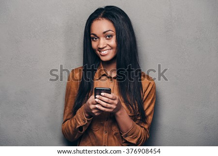 Message from friend. Beautiful young African woman holding smart phone and looking at camera while standing against grey background - stock photo