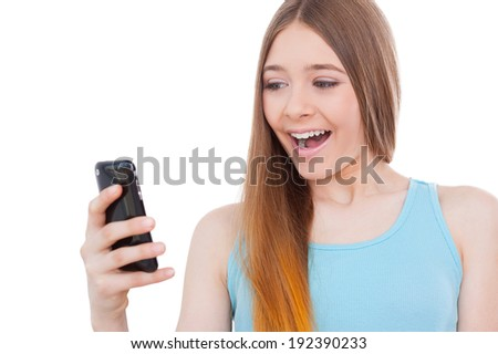 Message from him. Cheerful teenage girl holding mobile phone and looking at it with smile while standing isolated on white