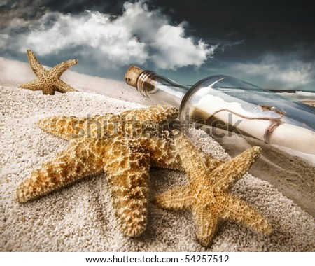 Message in a bottle buried in sand on a beach with dark skies - stock photo