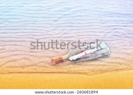 Message in a bottle on a sandy beach, conceptual image - stock photo