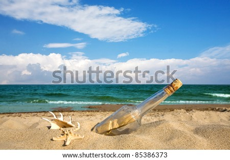Message in a bottle on an isolated beach - stock photo