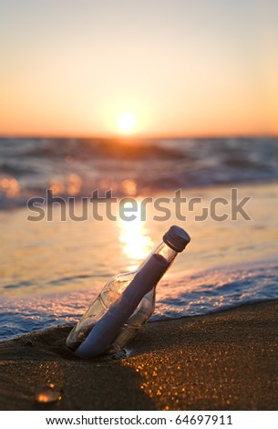 Message in a Bottle on sea beach - stock photo