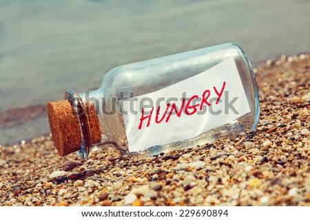 Message in a bottle saying Hungry. Hunger concept.  - stock photo