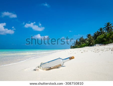 Message in a bottle washed ashore on a tropical beach. - stock photo