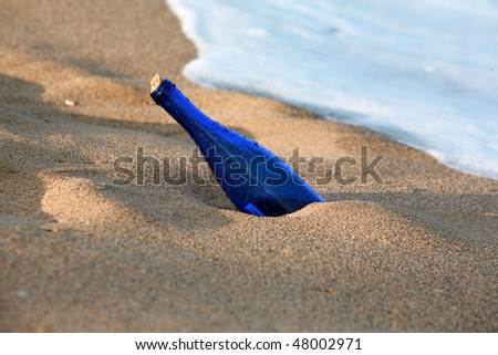 message in a bottle washes ashore in the tide - stock photo