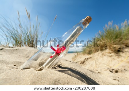 Message in a clear glass bottle washed up on the beach concept for sos, assistance, help and stranded - stock photo