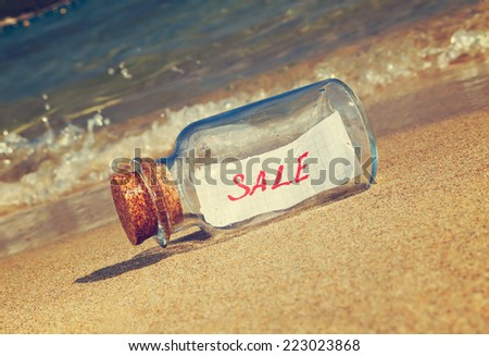 "Message in a vintage bottle ""Sale"" on beach. Creative marketing concept."