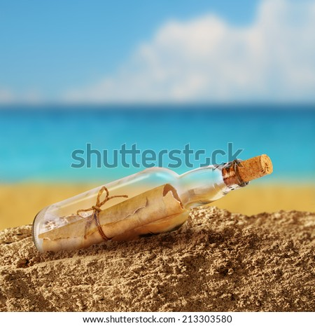 Message in the bottle on seashore beach sand - stock photo