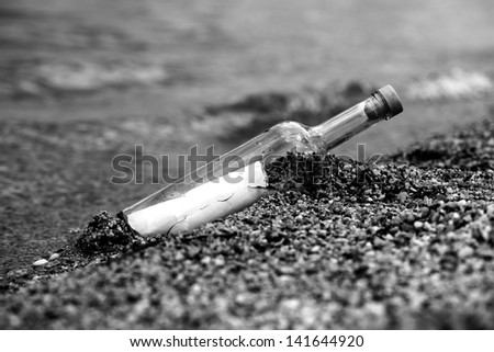 Message in the bottle on the beach, black and white photo - stock photo