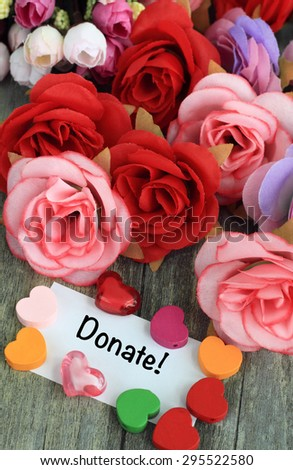 message of donation, with flowers and hearts in the background - stock photo