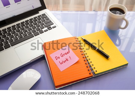 Message on paper with word Do Great Work ! on note stick on colorful book with laptop and a cup of coffee on glass table, top view image - stock photo