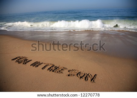 """Message says """"fun in the sun""""  in the Sand on a Beach with waves and blue ocean concepts - stock photo"""