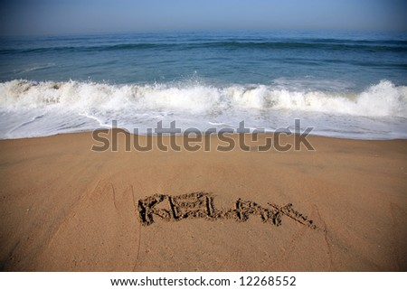 """Message says """"relax""""   in the Sand on a Beach with waves and blue ocean concepts - stock photo"""