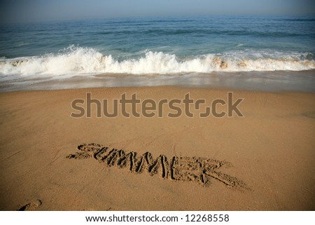 """Message says """"summer""""   in the Sand on a Beach with waves and blue ocean concepts - stock photo"""