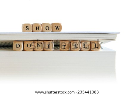 "message ""show don't tell"" for creative writing, spelled with wooden letter blocks on the top and between pages of a big white book or script stack, isolated on white, copy space"
