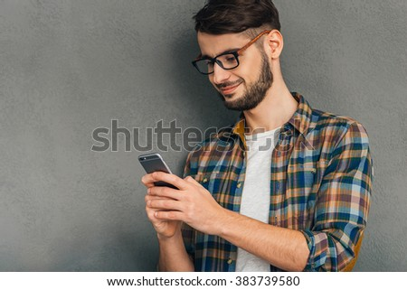 Message to her. Cheerful young man in glasses using his smartphone with smile while standing against grey background - stock photo