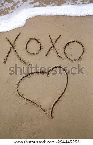 Message written in the sand kiss hug kiss hug and a drawing of a heart; message written in the sand about love with an ocean wave in the background with foamy bubbles - stock photo