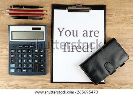Message You're Fired on clipboard on wooden table, top view - stock photo