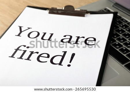 Message You're Fired on laptop keyboard, closeup - stock photo