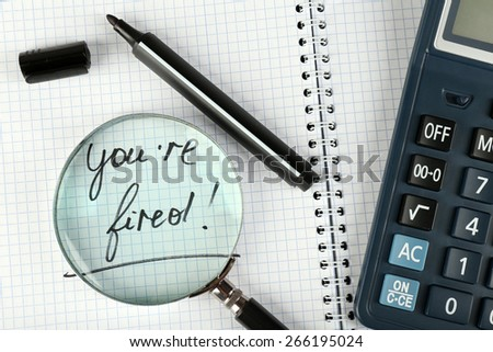 Message You're Fired on notebook with calculator, marker and magnifying glass on wooden table, closeup - stock photo