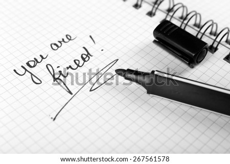 Message You're Fired on notebook with marker, closeup - stock photo