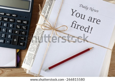 Message You're Fired on stack of newspapers, closeup - stock photo