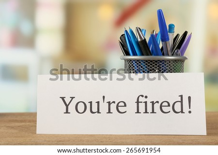 Message You're Fired on wooden table, on blurred background - stock photo