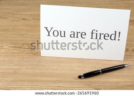 Message You're Fired with pen on wooden background - stock photo