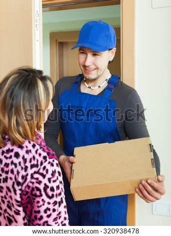 Messenger in uniform delivered box to woman at home - stock photo