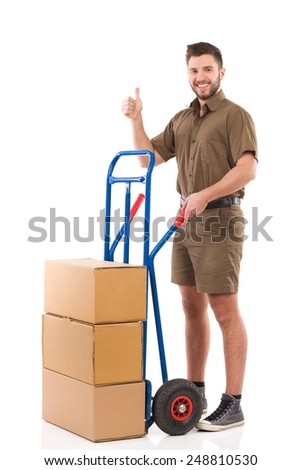 Messenger showing thumb up. Cheerful delivery man standing with a push cart and showing thumb up. Full length studio shot isolated on white. - stock photo
