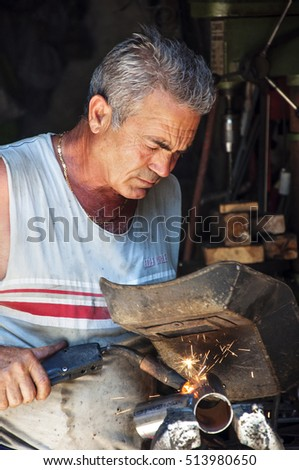 MESSINA, ITALY - JULY 15. Welder worker, craftsman in his workshop on July 15, 2010.