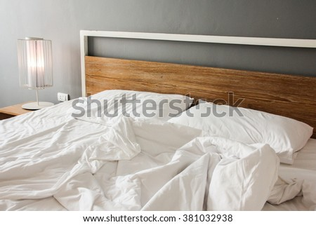 Messy and unmade bed in hotel room on morning time. - stock photo