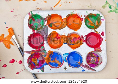 Messy array of colors of children's paint in a tray with a paint brush. - stock photo