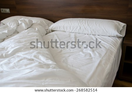 Messy bed at morning. Comfortable furniture to sleep at night - stock photo