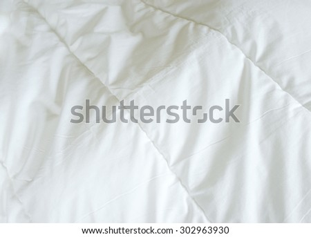Messy bed, white blanket for background. - stock photo