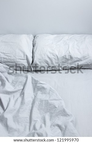 Messy bed with two pillows and gray bedclothes. - stock photo