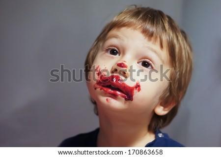 messy boy eating red ice cream - stock photo