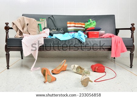Messy clothes, lady bag and shoes scattered on a leather sofa - stock photo