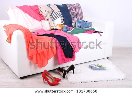 Messy colorful clothing on white sofa on white wall background - stock photo