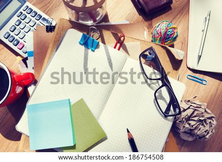 Messy Designer's Table with Blank Note and Tools - stock photo