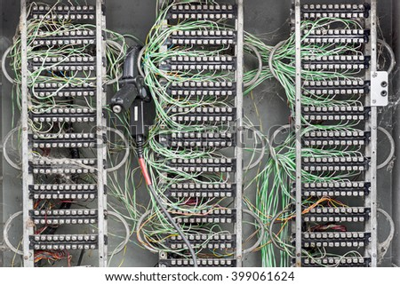 Messy dirty electric box with connections and colored wires - stock photo