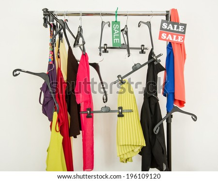 Messy rack of clothes and hangers after a big sale. Sale sign for summer clothes on a clearance rack with colorful summer outfits and accessories. - stock photo
