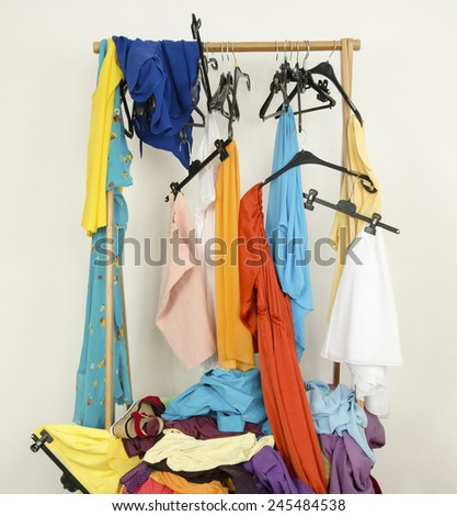 Messy rack of clothes and hangers. Untidy wardrobe with colorful summer outfits and accessories. - stock photo
