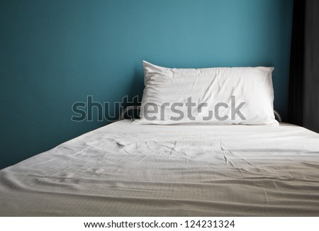 Messy white bed and one pillow , light blue wall in the morning - stock photo