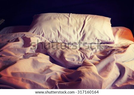 Messy white bed and pillow in the morning, vintage or retro color toned - stock photo