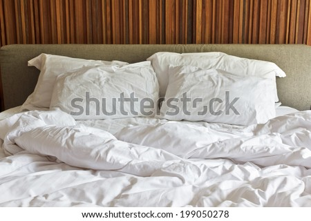 Messy white bed and two pillow, in the morning. - stock photo