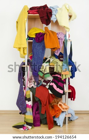 Messy winter clothes thrown on a shelf. Untidy cluttered wardrobe with colorful clothes and accessories. - stock photo