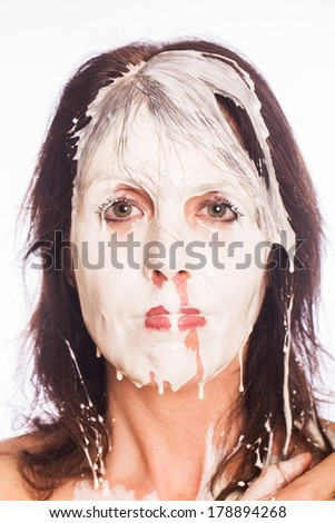 Messy woman with milk on her face. - stock photo