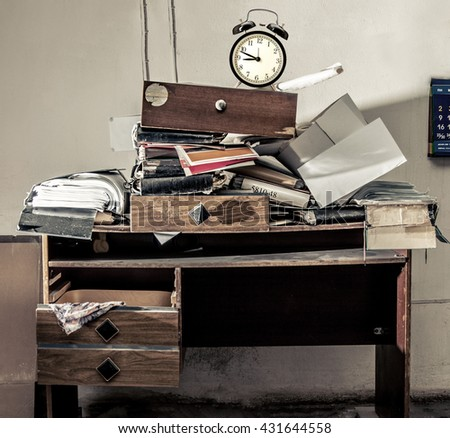 Messy workplace with stack of old paper and alarm clock - stock photo