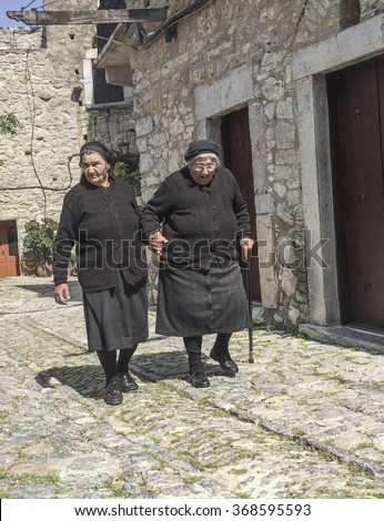 MESTA, CHIOS ISLAND, GREECE - APRIL 25, 2015; Senior women (widow) dressed in black, walking at street in Mesta town of Chios Island in Greece.